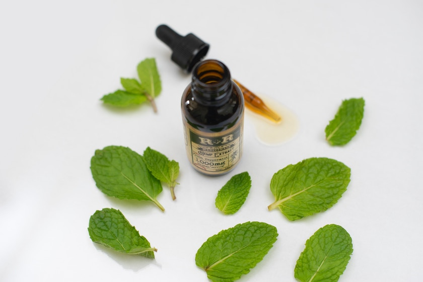 picture of peppermint essential oil with mint leaves surrounding