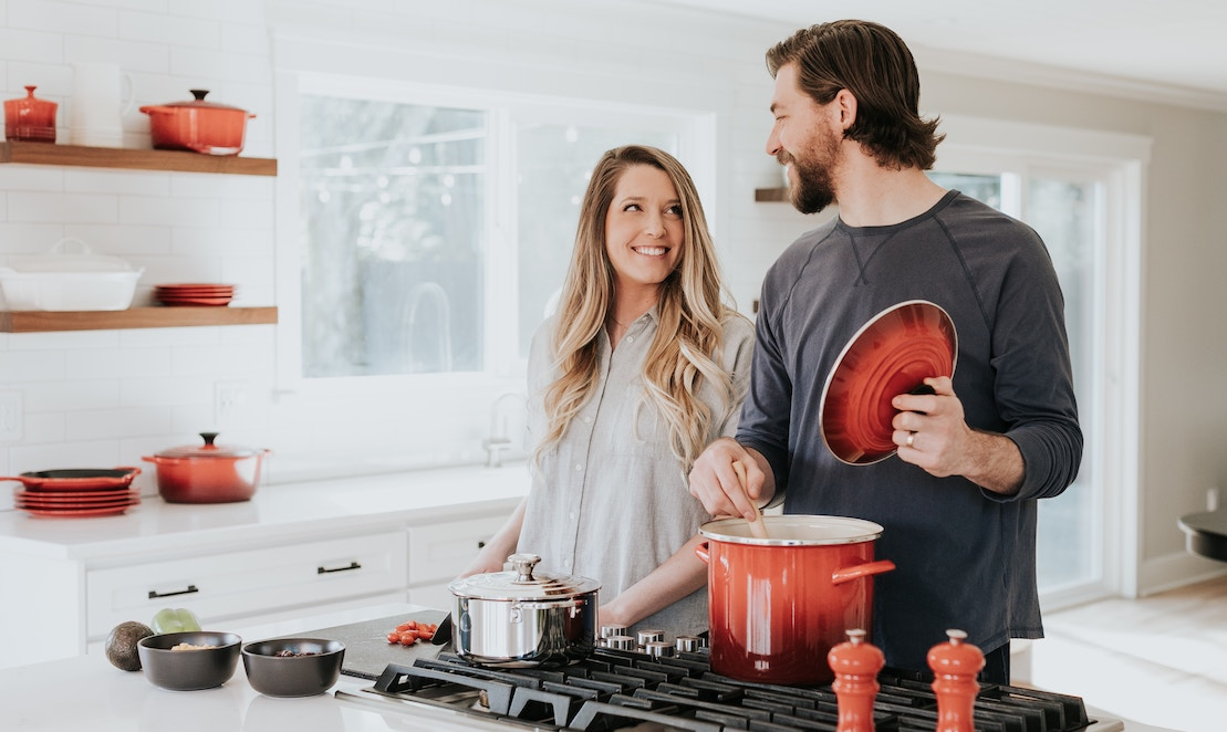 picture of woman and man cooking together with non-toxic cookware, red pots in background